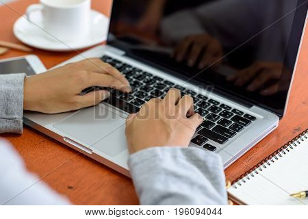 The Hand Of Beautiful Businesswoman Uses A Laptop Computer In The Office. With White Coffee Cup And