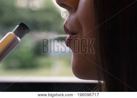 The girl smokes a hookah in a cafe. Close-up of a lips.