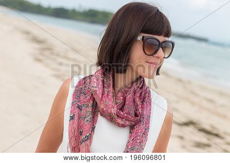 Portrait of young sexy attractive woman in white dress with silk scarf alone on the tropical beach of Bali Island, Indonesia.