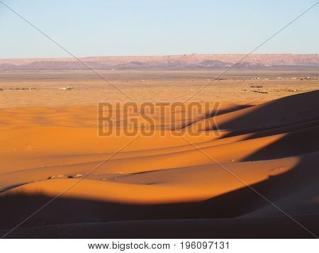 ERG CHEBBI dunes range near MERZOUGA city with landscape of sandy desert formations in southeastern MOROCCO near border with ALGIERIA, clear blue sky, 2017 warm sunny winter day, AFRICA on FEBRUARY.