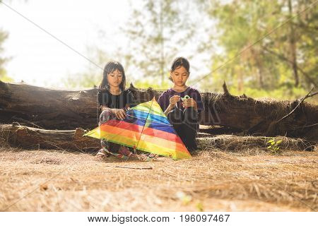 kampung Mek Mas Kota Bahru Kelantan / Malaysia - July 15 2017 : A shot of two young girls with sad faces trying to figure out how to fly the kite.