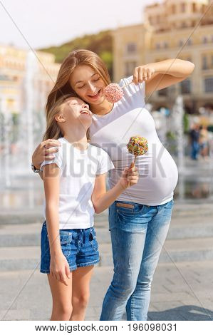 Cute little girl and her pregnant mother eating candy apples at fair in amusement park. Happy loving family. Mother and daughter having fun together