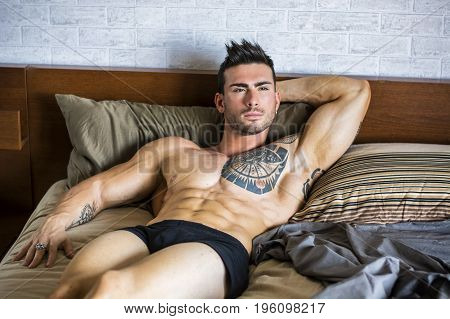 Shirtless sexy muscular male model lying alone on his bed in his bedroom, looking away with a seductive attitude
