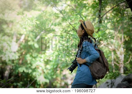 Beautiful Asian Girl Tourist Stands On A Rock To Photograph Nature With A Digital Camera Dslr In The