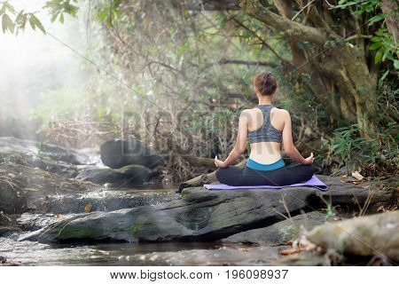 Asian Beautiful Women Yoga In Nature On The Rock And River Over Forest Background. Health And Fitnes