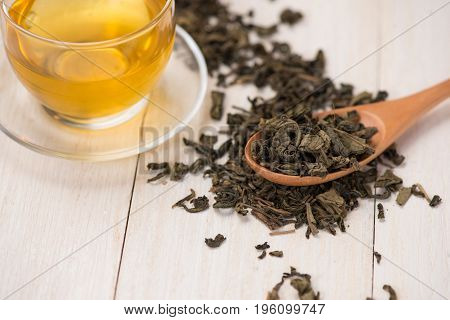 Black tea in a glass cup and tea leaves in wooden spoon on black stone background.