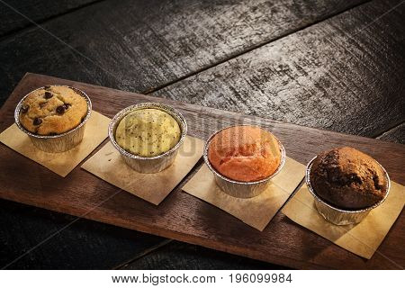 mixed freshly baked muffins on table in cozy coffeeshop interior