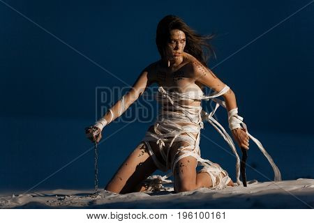 Girl in image of Egyptian mummy kneels on sand with metal chain and knife in her hands. She is wrapped in bandages and she has hieroglyphics on her body.