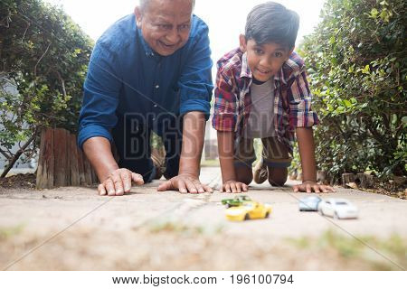 Boy and grandfather playing with toy cars while kneeling on pavement in yard