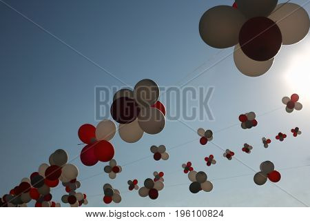 Flying colorful balloons against blue sky. Multi colored garland of balloons. A beautiful decoration for a street festival. Symbolizes freedom and endless possibilities
