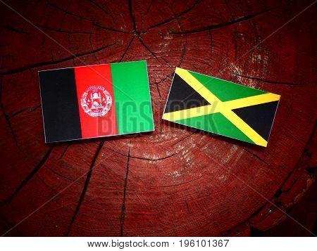 Afghani Flag With Jamaican Flag On A Tree Stump Isolated