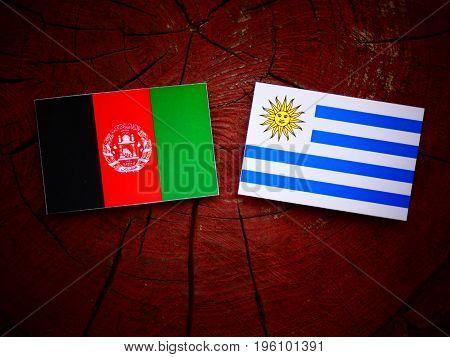Afghani Flag With Uruguaian Flag On A Tree Stump Isolated