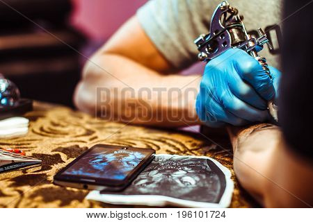 Russia Novokuzneck 5.07.2017: The tattoo artist makes a tattoo on the client's neck in the tattoo salon. The master does a tattoo in the studio. Close-up. Hard. Pain.