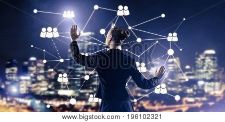 Back view of businesswoman against night cityscape working with social connection media concept