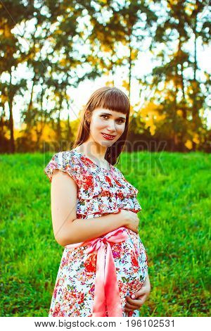 Young happy pregnant woman relaxing and enjoying life in nature. Outdoor shot. Copyspace