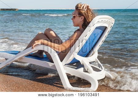 Pensive young woman in sunglasses is sitting in a deckchair against the background of the sea and tropical beach with palm trees.