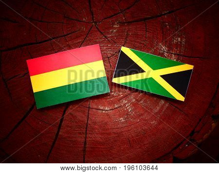 Bolivian Flag With Jamaican Flag On A Tree Stump Isolated