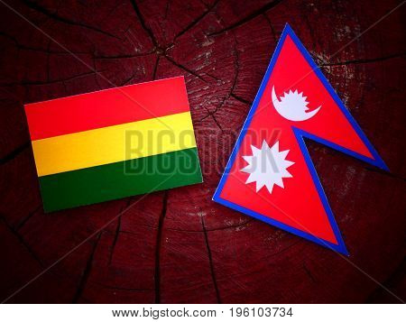 Bolivian Flag With Nepali Flag On A Tree Stump Isolated