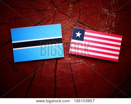 Botswana Flag With Liberian Flag On A Tree Stump Isolated