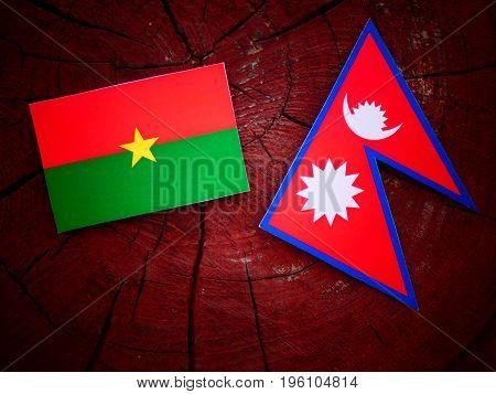 Burkina Faso Flag With Nepali Flag On A Tree Stump Isolated