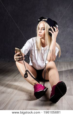 Young woman with headphones sitting on a floor near the wall.