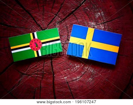 Dominica Flag With Swedish Flag On A Tree Stump Isolated
