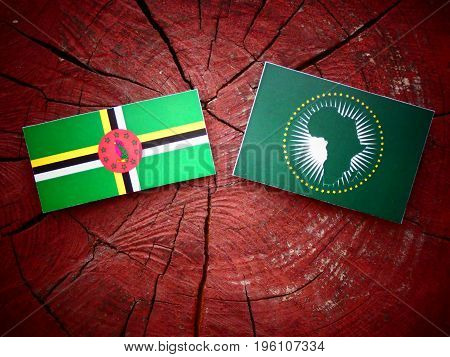 Dominica Flag With African Union Flag On A Tree Stump Isolated