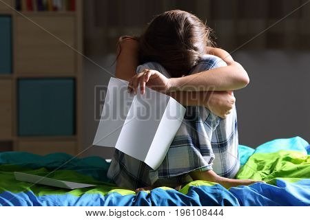 Front view of a single sad teen lamenting sitting on her bed after reading a letter with a dark light in the background