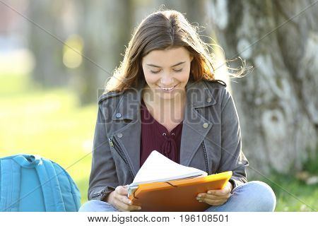 Single student girl studying reading notes sitting on the grass in a park