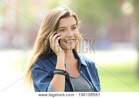 Portrait of a happy teen girl calling on phone and walking outdoors in a park