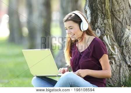 Single teen listening and watching media content on line with headphones and a laptop