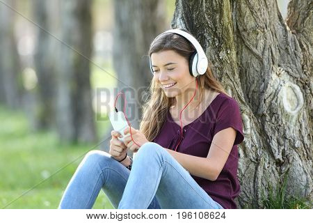 Single teen listening to music on line with headphones and smart phone sitting on the grass in a park