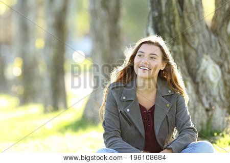 Front view of a single teen sitting and thinking looking at side outside in a park