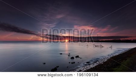 Fishnets and rocks in a calm sea under an orange and purple sunrise with a star-shaped sun just above the horizon
