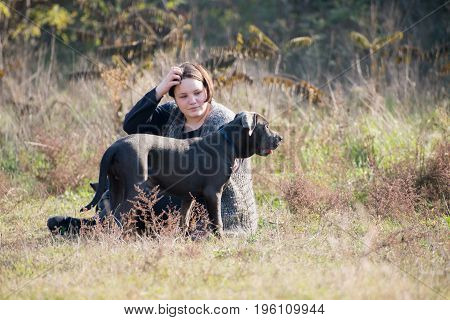 Girl with her gray Italian mastiff puppy