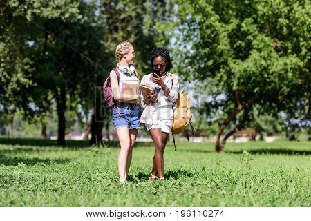 Beautiful Young Multiethnic Students Smiling And Talking While Walking In Park