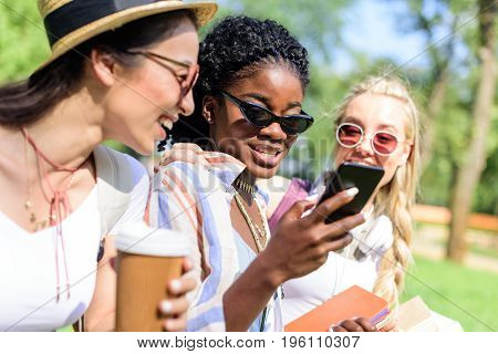Smiling Multiethnic Girls Using Smartphone And Drinking Coffee From Paper Cup In Park