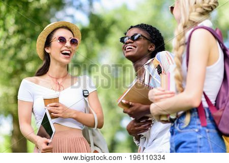 Smiling Young Multiethnic Women Holding Books And Digital Tablet While Talking In Park
