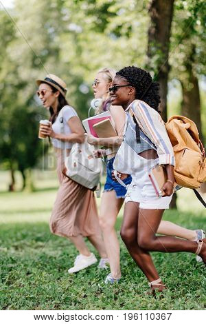 Multiethnic Girls In Sunglasses Holding Books And Running In Park