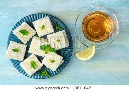 An overhead photo of a plate of cucumber sandwiches, shot from above on a teal blue texture with a cup of tea, a lemon slice, and a place for text