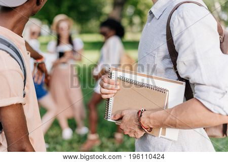 cropped shot of young students holding notebooks while standing in park