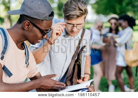 Two Multiethnic Boys Reading Book Together In Park