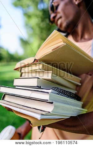 Close-up View Of Young African American Man Holding Pile Of Books In Park
