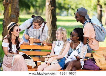 Young Multiethnic Students Holding Books And Digital Devices While Interacting In Park