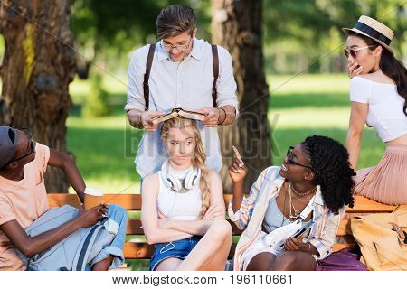 Young Multiethnic Students Having Fun While Studying Together On Bench In Park