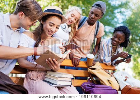 Cheerful Young Multiethnic Students Reading Books Together On Bench In Park