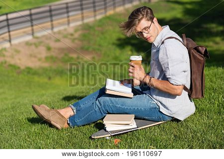 Handsome Young Man In Spectacles Reading Book And Drinking Coffee While Sitting On Skateboard In Par