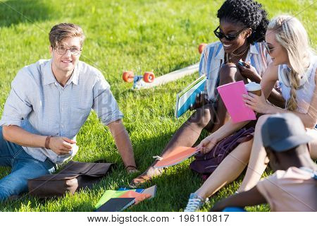 Happy Young Multiethnic Students Talking And Studying Together In Park