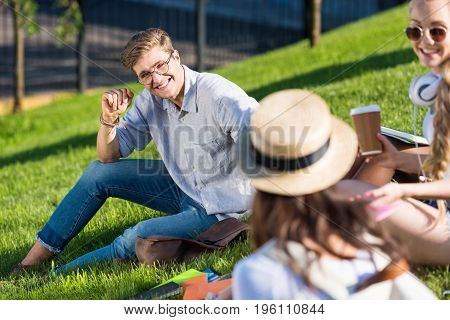 cheerful young students talking while sitting on green grass in park