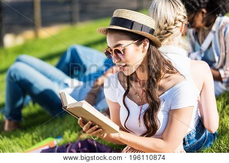 Smiling Young Asian Woman In Sunglasses And Straw Hat Reading Book While Sitting On Grass With Class